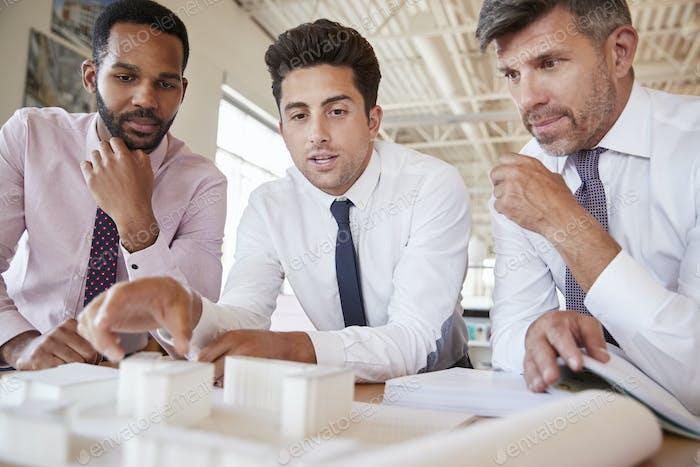 Drei männliche Kollegen diskutieren ein Architekturmodell