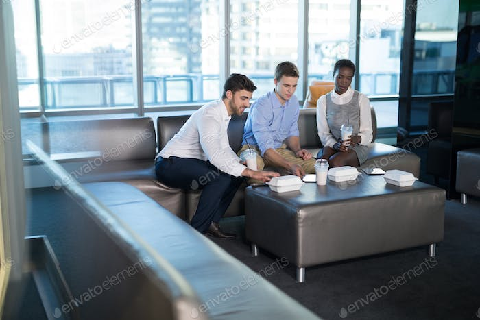Male and female executives having snacks