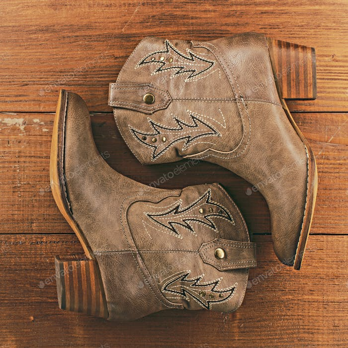 Retro cowboy boots on wooden background