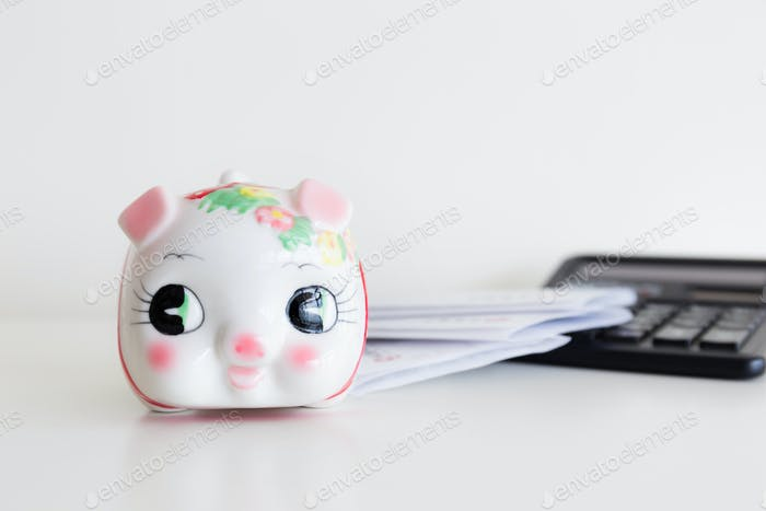 Piggy bank, calculator and statement