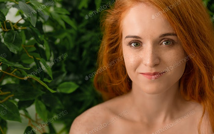Young redhead woman touching her face, green background