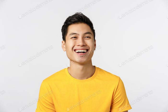 Friendship, joy and happiness concept. Cheerful young asian man in yellow t-shirt, look away as