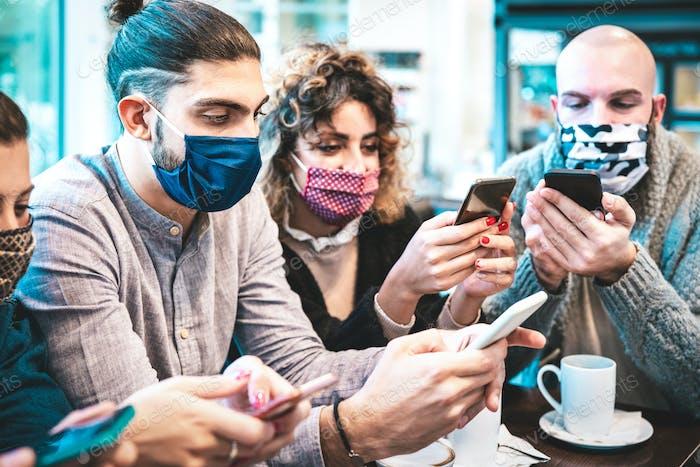 Besorgte Menschen mit Gesichtsmaske überprüfen Nachrichten auf Mobiltelefonen