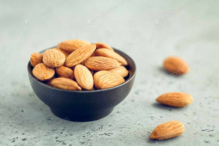 Fresh almond nuts in a back bowl on a textured grey table.