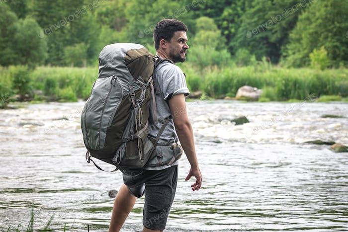 A hiker with a large hiking backpack on a hike.