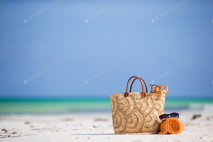 Beach accessories - toy plane, straw bag, orange towel and unglasses on the beach