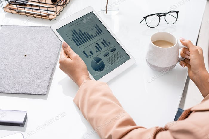 Hands of young businesswoman or banker with tablet analyzing financial data