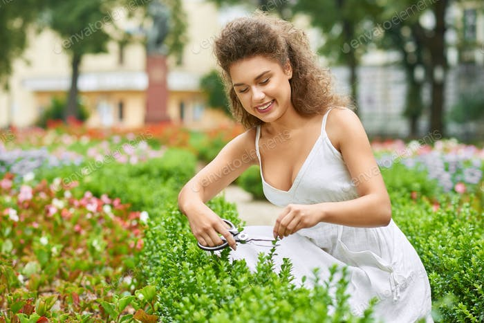 Attractive young woman working at her garden