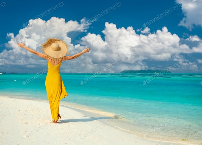 Woman in dress walking on tropical beach