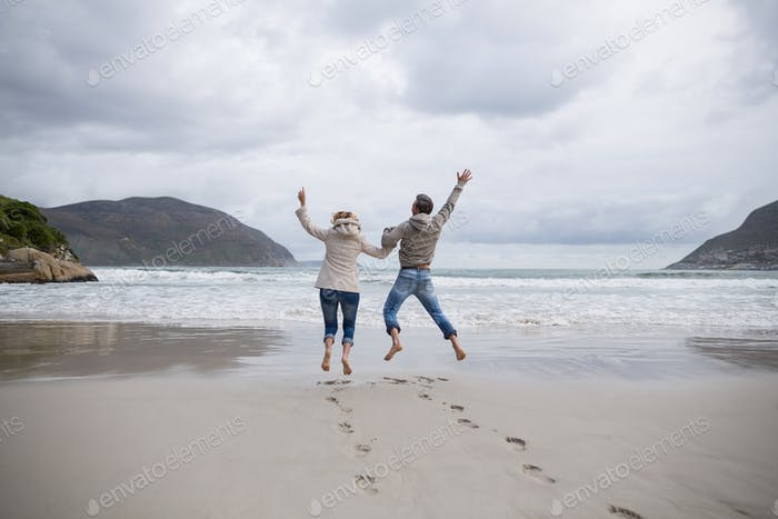 Mature couple jumping in air on the beach