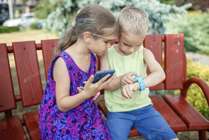 Kids using smartwatches with interest, care and parents control, new technology for children