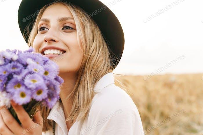 Bild der jungen blonden Frau mit Blumen lächelnd auf goldenes Feld