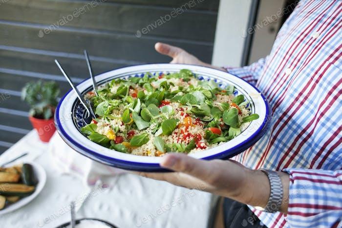 Mittelteil des Menschen hält Salatplatte auf Hof
