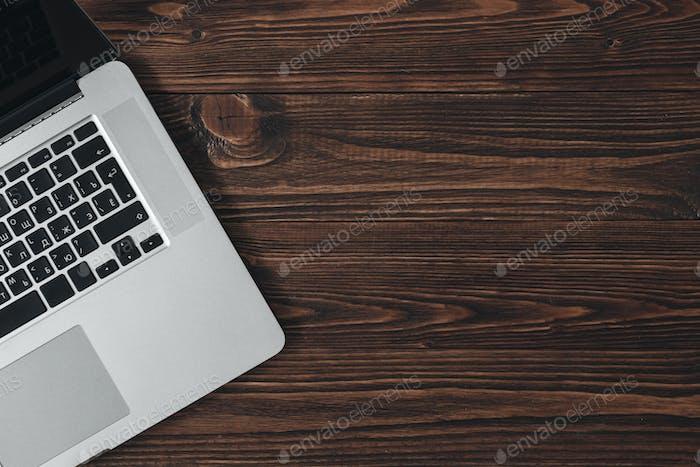 Laptop auf dem braunen Holzschreibtisch