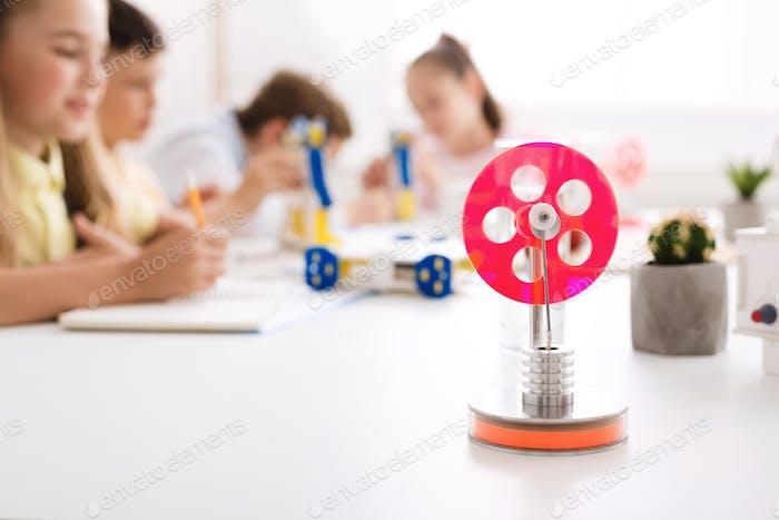 Stammbildung. Roboterrad auf dem Schreibtisch, Kinder studieren