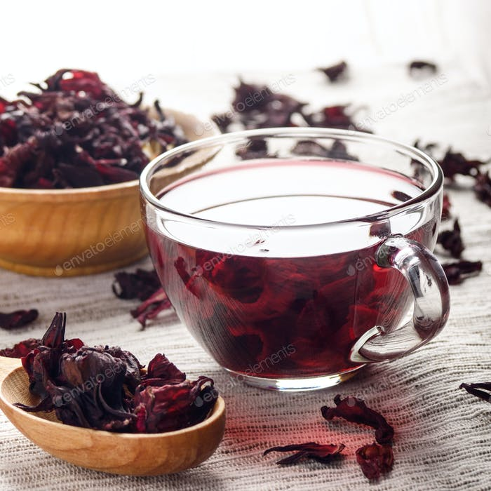 Closeup view at wooden bowl tea cup and spoon of dry hibiscus pe