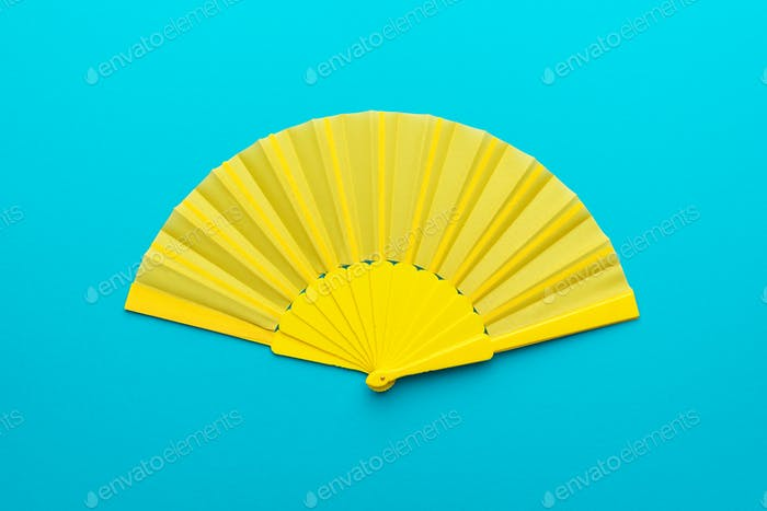 Top View Of Opened Yellow Hand Fan On Turquoise Blue Background With Copy Space