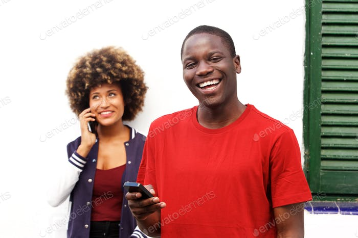 happy man smiling with mobile phone and woman making a phone call in background