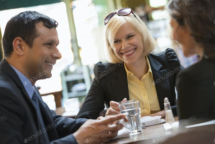 Business people a man and two women sitting at a table. A meeting or social gathering.