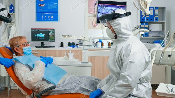 Assistant in protective equipment putting dental bib to patient
