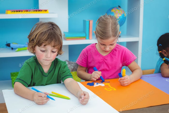 School kids making art at their desk in class