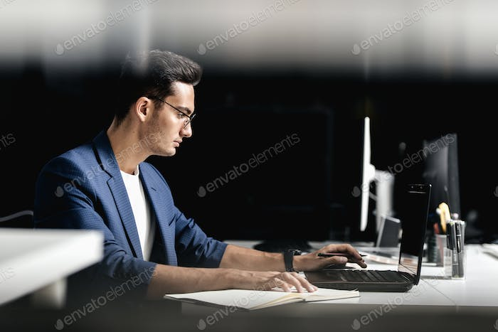 Architect in glasses dressed in blue checkered jacket makes notes in a notebook on the desk with