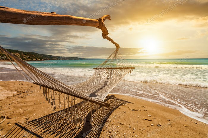 Hammock on the beach at sunset. Summer vacation on tropical resort