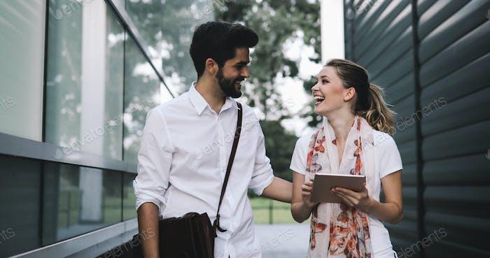 Glückliche Geschäftskollegen lächeln und reden in einer Pause