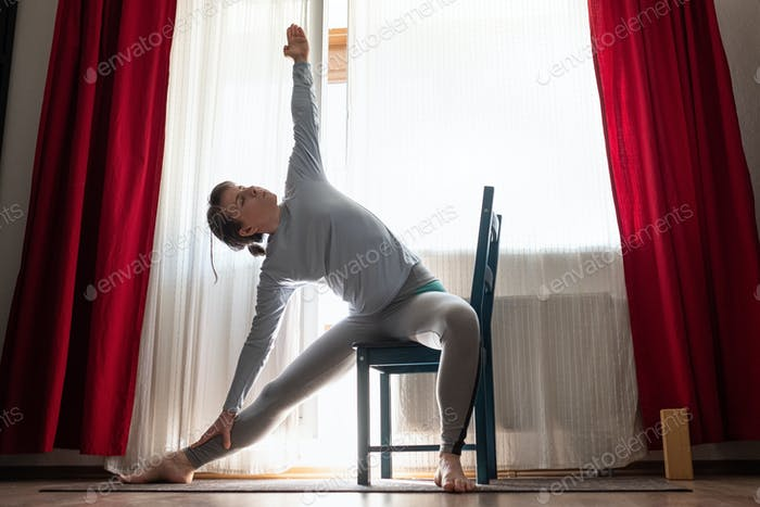 Sporty attractive young woman doing side bend, Trikonasana posture