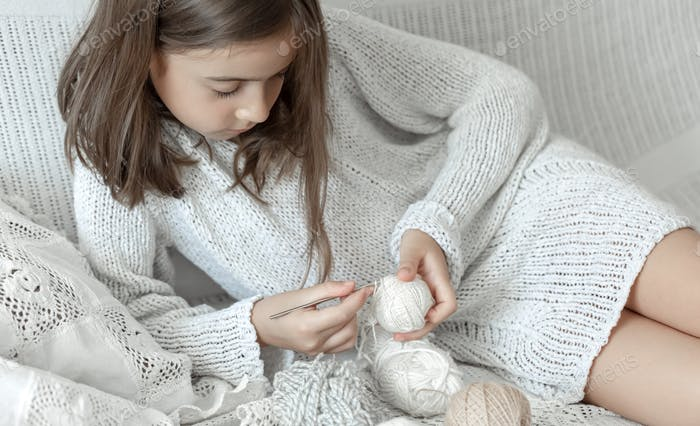 A little girl at home on the couch learns to crochet.