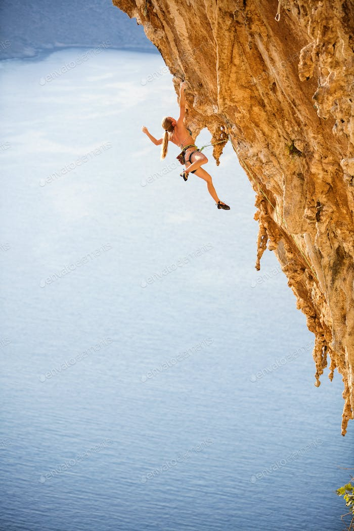 Young female rock climber in bikini hanging with one hand
