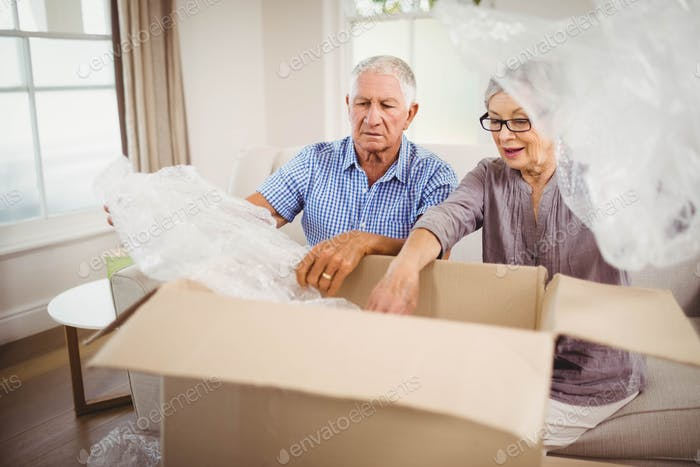 Senior couple unpacking a cardboard box in living room