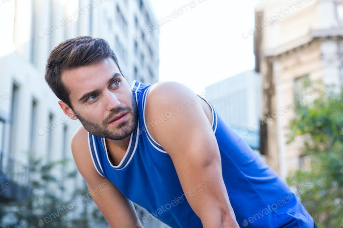 Determined handsome athlete looking away in the city