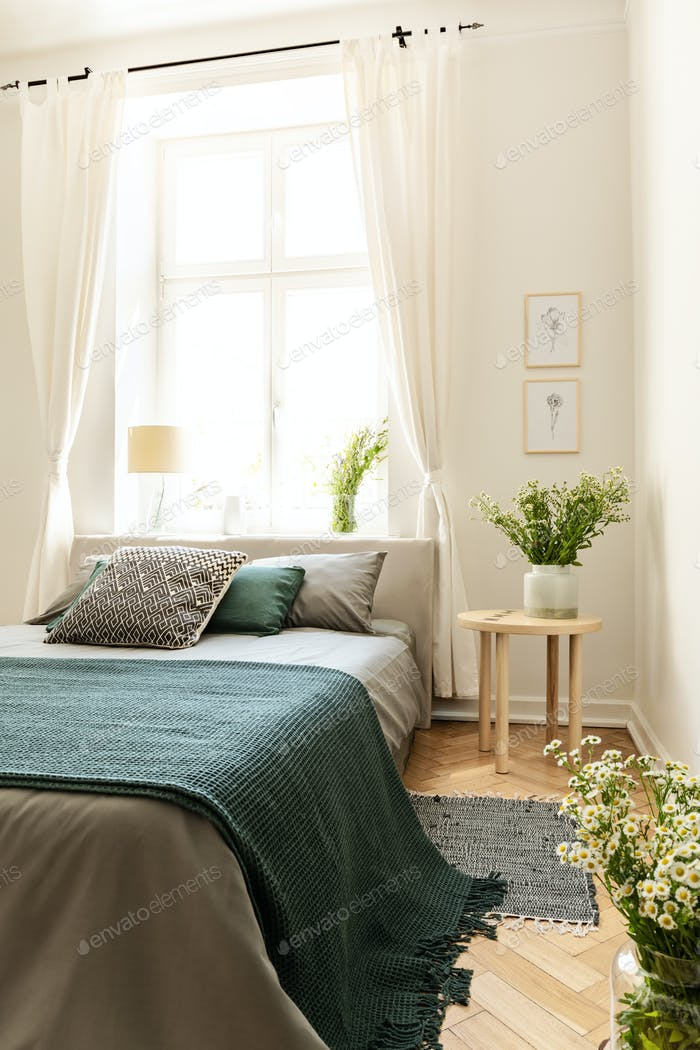 Green blanket on bed next to table with plant in bedroom interio