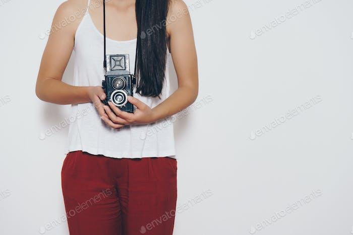 Mujer sosteniendo una cámara Vintage frente a un Fondo blanco