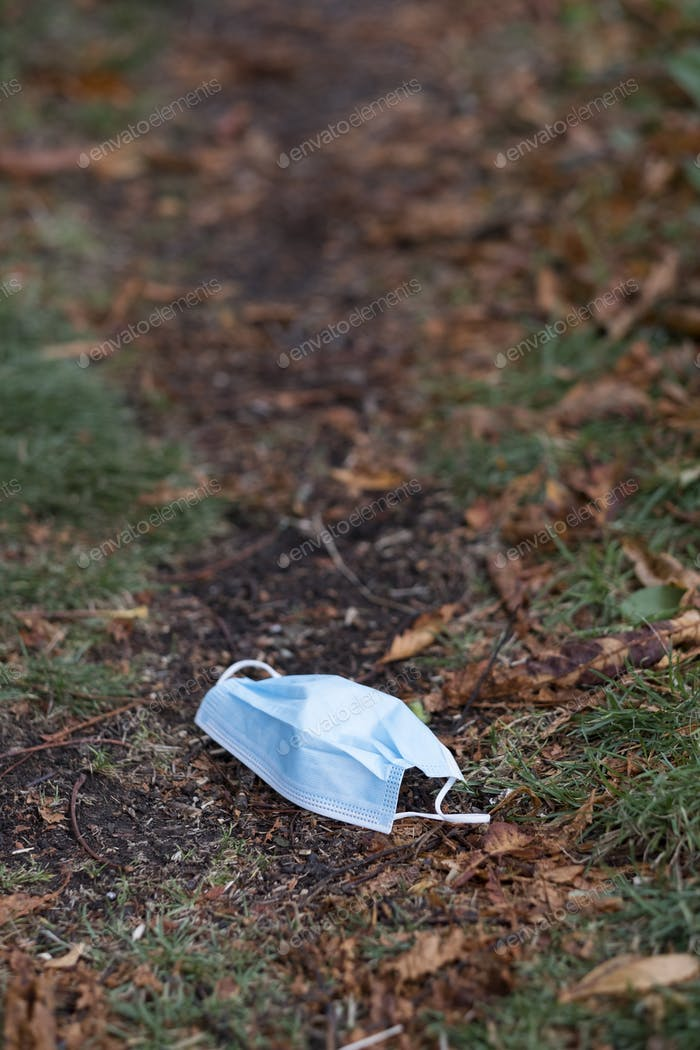High angle close up of disposed blue surgical face mask lying on ground.