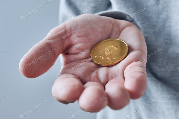 Hand offering Ethereum cryptocurrency coin