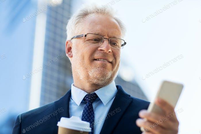 homme d'affaires avec smartphone et café en ville