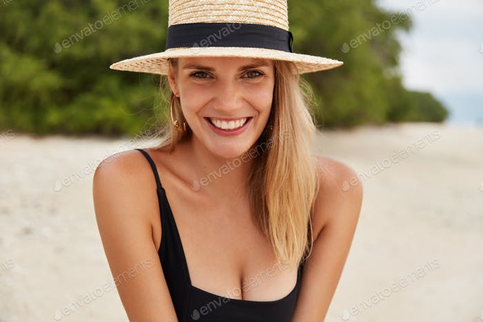 Horizontal portrait of glad satisfied woman has attractive look, wears fashionable hat and swimming