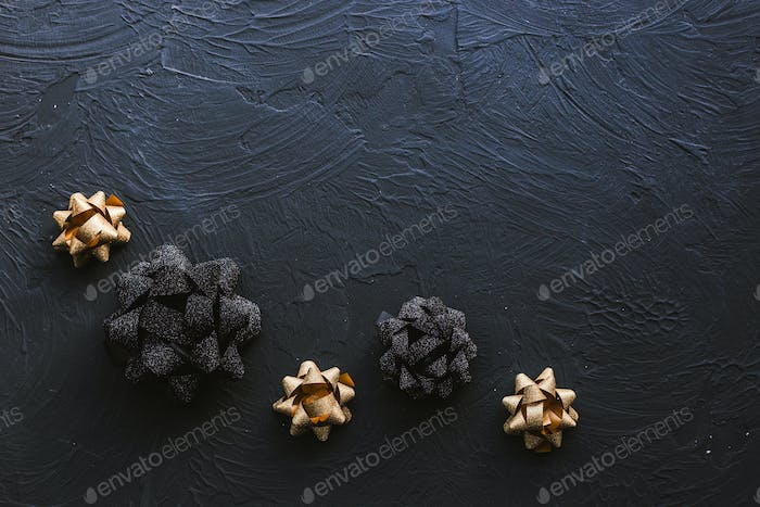 Gold and black bow for gift box on a black background. Christmas.