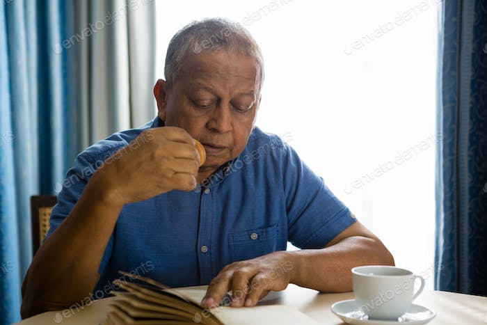Senior man eating food while reading book in nursing home