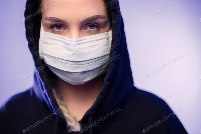 Serious caucasian woman in protective face mask with blue color lights
