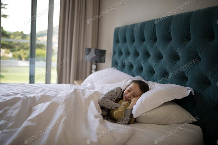 Girl sleeping on bed with teddy bear in bedroom
