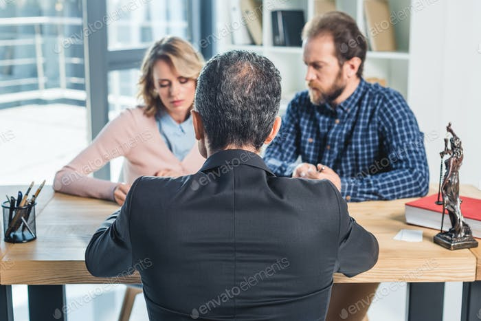 selective focus of couple having meeting with lawyer in office