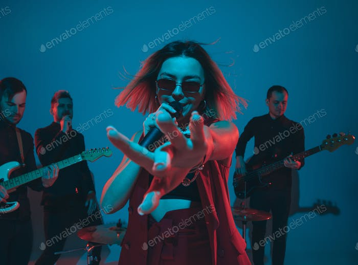 Young caucasian musicians, band performing in neon light on blue studio background, singer in front