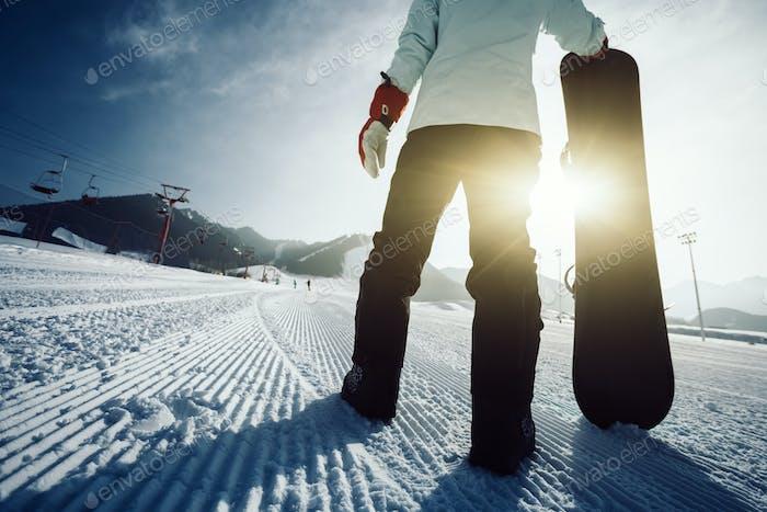 Snowboarder with snowboard at ski resort