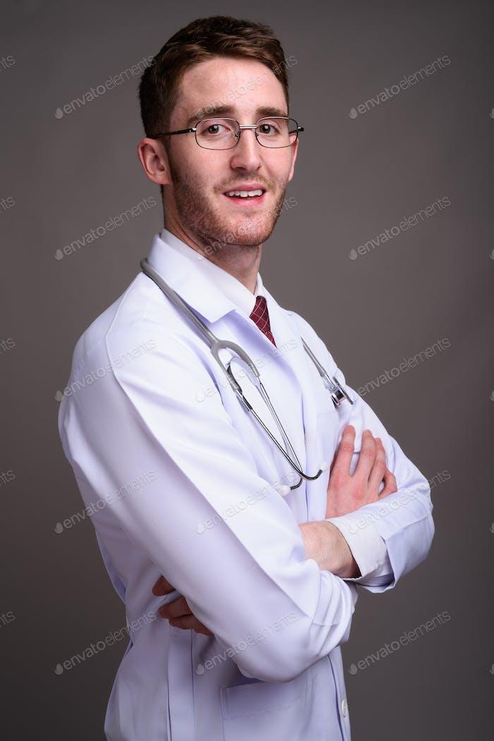 Young handsome man doctor wearing eyeglasses against gray backgr