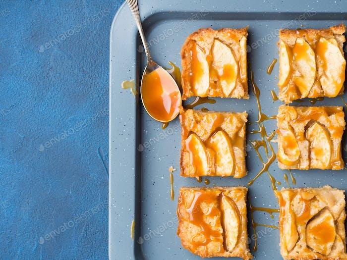 Apfelblonde Brownies mit Karamell auf Tablett blauem Hintergrund