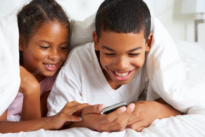 Two Children Using Mobile Phone Under Duvet