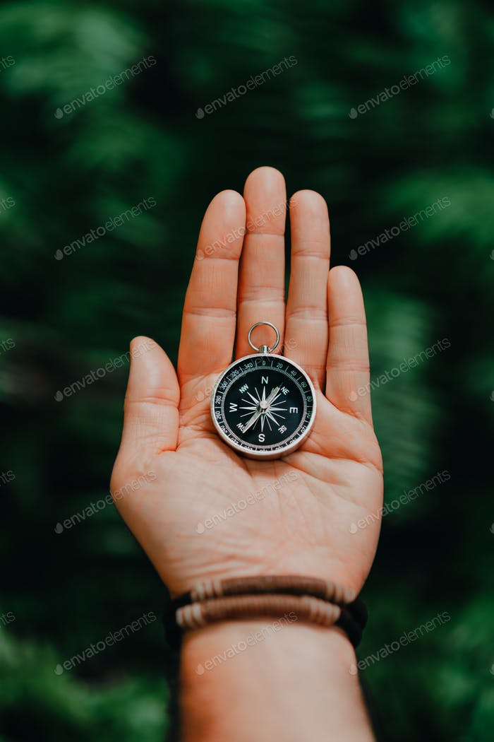 Hand with compass against tropical forest jungle terrain. POV Travel concept